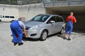 Zwei Inhaftierte reinigen im Innenhof einen Opel.